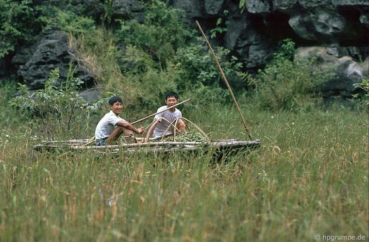 Two men on a simple bamboo boat
