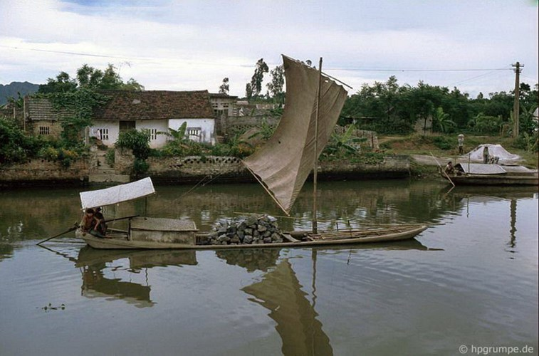 Wooden boat transporting stone in the river